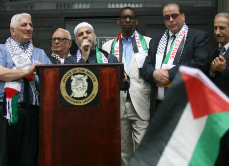 Imam Mohammad Qatanani speaks before the raising of the Palestinian flag outside Paterson City Hall. Paterson Mayor Jeffrey Jones is on the right.