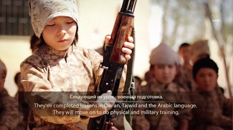 The video immediately cuts to a young boy, pictured, field-stripping and rebuilding  an AK-47 assault rifle