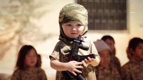 The propaganda video shows a toddler brandishing a toy sub-machine gun while wearing military fatigues