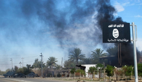 Smoke rises behind an Islamic State flag after Iraqi security forces and Shiite fighters took control of Saadiya in Diyala province from Islamist State militants, Nov. 24, 2014. (photo by REUTERS)