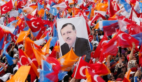 Supporters hold up a portrait of Turkey's Prime Minister Recep Tayyip Erdogan while waving Turkish and Justice and Development Party (AKP) flags during an election rally in Istanbul, March 23, 2014. (photo by REUTERS/Murad Sezer)